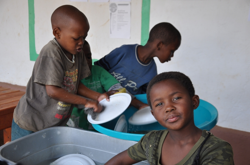 S Africa, children washing plates 1
