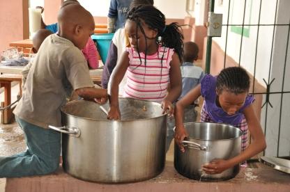 S Africa, children wasking pots