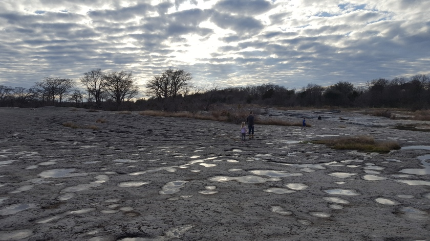 mckinney falls, guthrie w children on rock bed w spotted sky