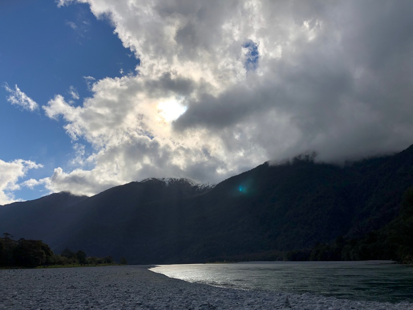 NZ, beach w snow-topped mountains, sun in clouds