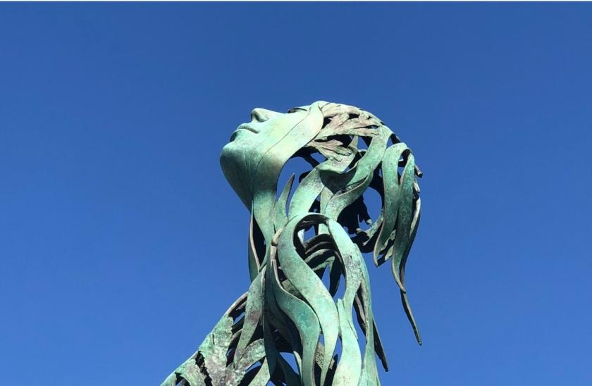 Metal female sculpture looking up, Laguna Beach, CA