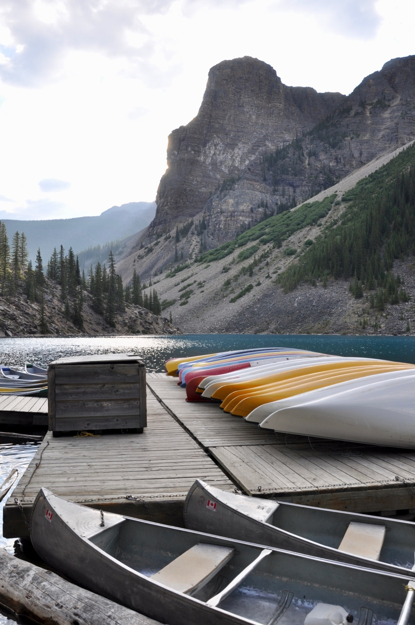 Empty canoes lined up at lake, ready to go, Canadian rockies